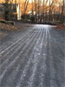 Town road treated with brine solution pre-snowstorm